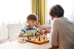 grandmom with grandson play chess together at home. quarantine. health concept. Corona Virus.  Quality Time. Family having fun playing at home. stay home concept