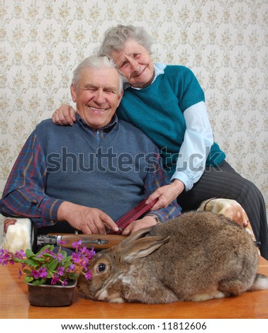 grandmother and grand-dad laugh at a rabbit
