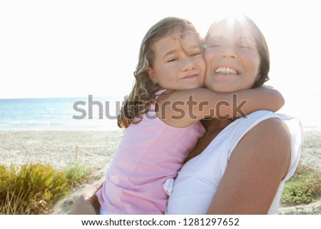 Grandmother and grand daughter enjoying sunny beach holiday heads together, joyful smiling with sunny sky, outdoors. Senior and child playful fun bonding family travel activities lifestyle.