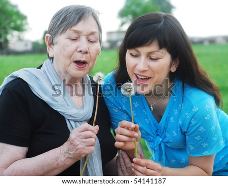 grandmother and grand daughter with dandelions on the meadow
