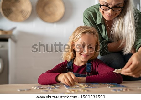 Grandmother and granddaughter doing puzzle together at home. Senior woman helping smiling little girl to solve puzzles. Happy grandchild solving puzzle at home while mature granny, playing together.