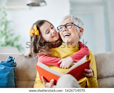 Grandmother and granddaughter having fun together and reading a book at home Foto stock ©