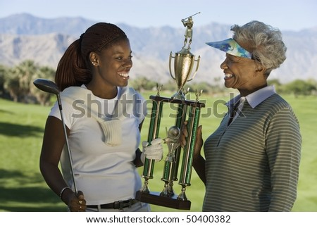 Grandmother and granddaughter holding golf trophy, smiling