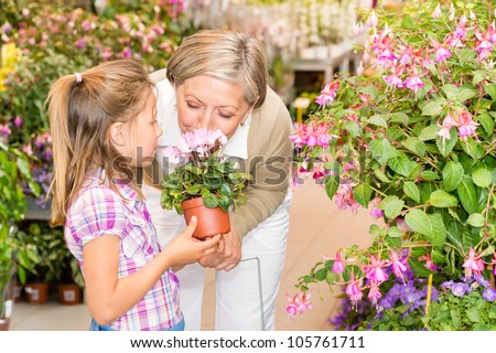 Grandmother and granddaughter holding pink potted flower at garden center