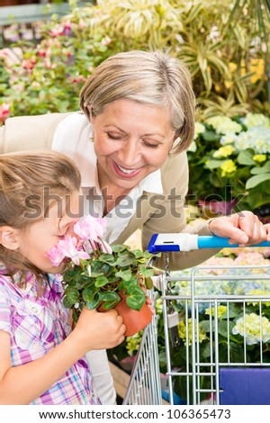 Grandmother and granddaughter holding pink potted flower at garden centre