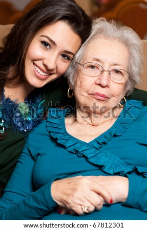 Grandmother and granddaughter in an affectionate lifestyle pose in a home setting.
