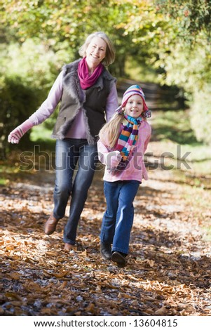Grandmother and granddaughter playing in autumn woods