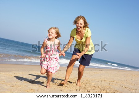 Grandmother And Granddaughter Running Along Beach - stock photo