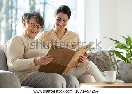 Grandmother and granddaughter smiling together while looking at family pictures