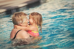 Grandmother and granddaughter swimming at pool