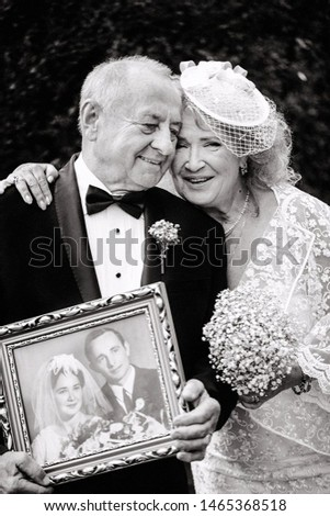 grandmother and grandfather holding their wedding photo after 50 years. elder couple wedding. golden wedding anniversary celebration. grannie and grandpa wedding. 50 years together. old couple married