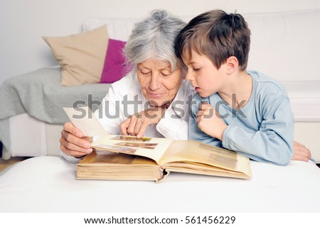 Grandmother and grandson are looking at an photograph album together