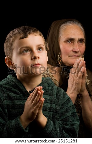 Grandmother and grandson praying together