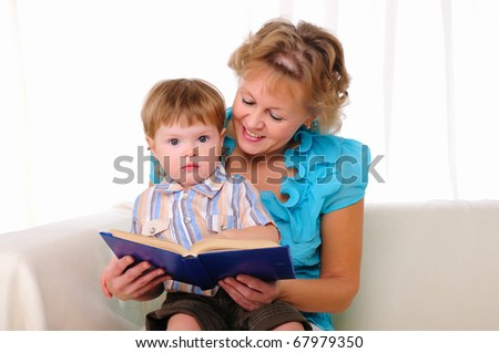 Grandmother and grandson reading a book together. Symbol of the family.
