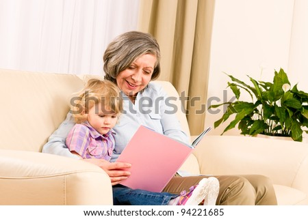 Grandmother and little girl reading book happy together at home