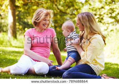 Grandmother And Mother Playing With Baby Son Outdoors In Garden