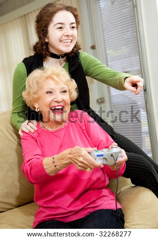 Grandmother and teen granddaughter having a great time playing video games.