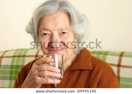 Grandmother drinks a glass of fresh water