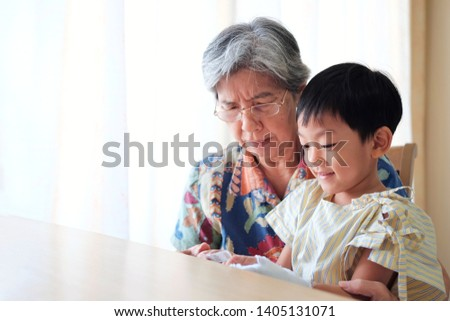 Grandmother embrace her nephew carefully in her arm. Asian patient kid 4 year old smile and sit with grand ma in hospital room and show bandage. Concept recovery and Encouragement, get well soon,  #1405131071