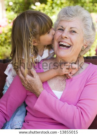 Grandmother getting a kiss from granddaughter