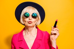 Grandmother getting ready for date! Charming, attractive old woman holding red lipstick pouting lips for a kiss isolated on brigth yellow background