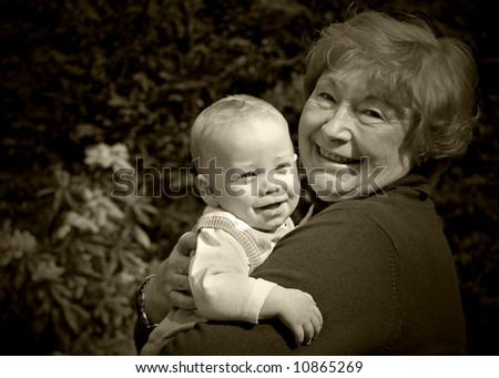 Grandmother holding happy grandson in the garden