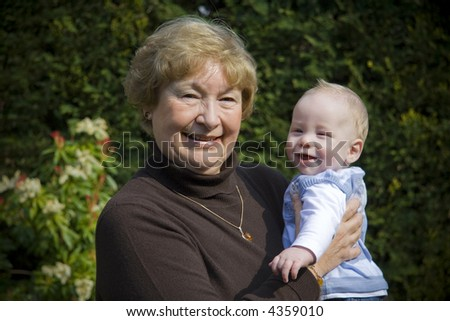 Grandmother holding her grandson portrait in garden