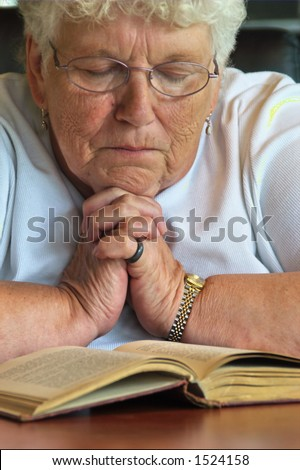 Grandmother holding her hands in prayer.
