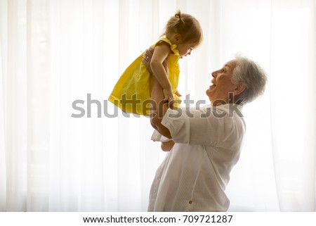 Grandmother holding little granddaughter in the room at home Foto stock ©