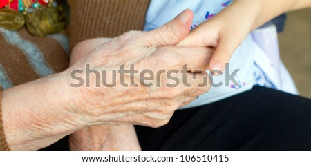 Grandmother holds the hand of his grandson