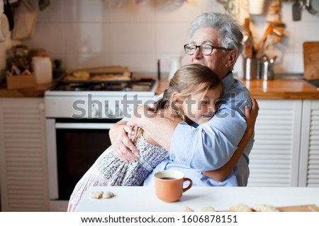 Grandmother hug child girl. Kid and senior woman baking in cozy home kitchen. Happy family enjoying kindness, tenderness, embracing. Lifestyle moment.