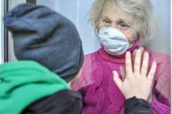 Grandmother in a respiratory mask communicates with her grandson through a window. Elderly quarantined, isolated. Pandemic coronavirus covid-19. Caring with older people. Family values