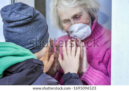 Grandmother in a respiratory mask plays with hands with her grandson through a window. Elderly quarantined, isolated. Pandemic coronavirus covid-19. Caring with older people. Family values Foto stock ©