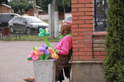 Grandmother in bright cloth selling balloons on the  street, Ukraine