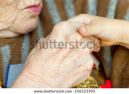 Grandmother kisses the hand of his grandson. Veteran of World War 2