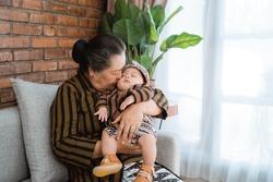 grandmother kissing sleeping little grandson when sits on sofa,wearing javanese batik at home