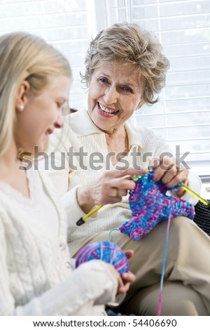 Grandmother knitting with granddaughter, focus on senior woman