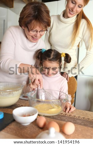 grandmother making crepes with little granddaughter