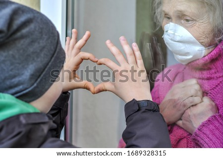 Photo of Grandmother mature woman in a respiratory mask communicates with her grandchild through a window. Elderly quarantined, isolated. Coronavirus covid-19. Caring with older people. Family values, love