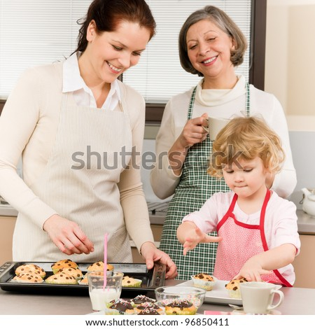 Grandmother, mother and child girl making cupcakes in kitchen