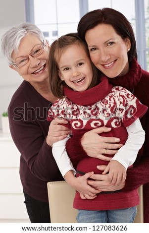 Grandmother, mother and daughter smiling, hugging.