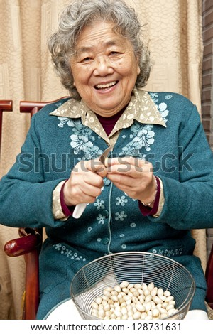 Grandmother peeling nut fruit