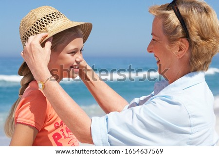 Grandmother placing sun hat on granddaughter's (7-9) head at beach