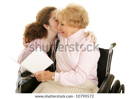 Grandmother reading a greeting card and getting a kiss from her teen-aged granddaughter.  Isolated on white.