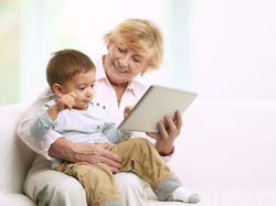 Grandmother reading a tale to her grandson from a digital tablet