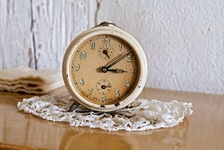 grandmother's old alarm clock on a lace doily