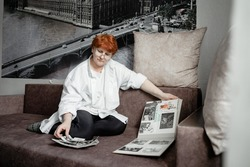 grandmother sits on the couch and looks at photos of her youth, nostalgic for the old days, the city of Kemerovo February 25, 2021