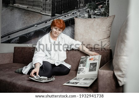 grandmother sits on the couch and looks at photos of her youth, nostalgic for the old days, the city of Kemerovo February 25, 2021 Foto stock ©