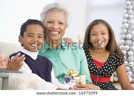 Grandmother Sitting With Her Two Grandchildren,Holding A Christmas Gift