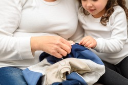 Grandmother teaches her granddaughter to mend clothes. Sustainability living, repairing clothes, shopping less concept.